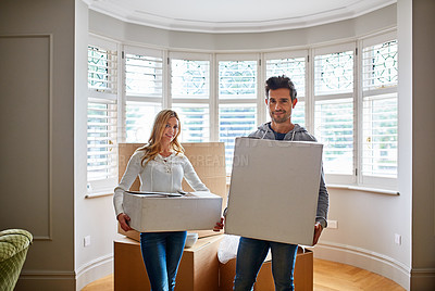 Buy stock photo Portrait of a happy young couple carrying boxes in their new house