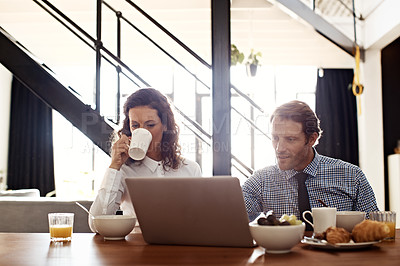 Buy stock photo Shot of a professional couple sitting at the dining table eating breakfast and using a laptop