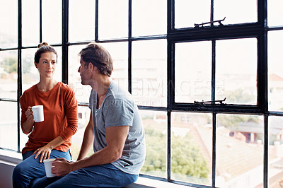 Buy stock photo Shot of a happy mature couple sitting on a window sill at home drinking coffee and talking together