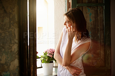 Buy stock photo Shot of an attractive young woman standing by a window at home talking on a cellphone