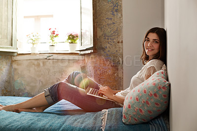 Buy stock photo Portrait of a smiling young woman lying on her bed using a laptop