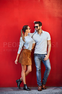 Buy stock photo Shot of a stylish young couple leaning against a red wall outside