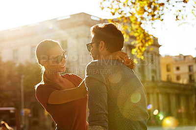 Buy stock photo Shot of an affectionate young couple enjoying a day together in the city