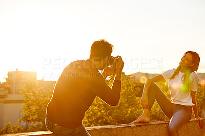 Buy stock photo Shot of a young man taking a photo of his girlfriend while sitting on a balcony overlooking the city at sunset