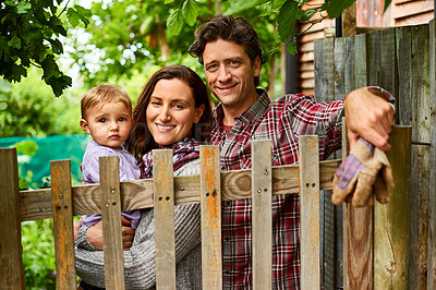 Buy stock photo Portrait of a couple with their baby girl standing their organic garden