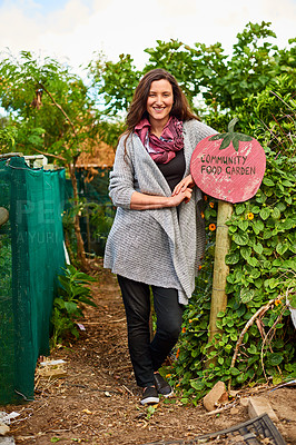 Buy stock photo Portrait of a mature woman standing outside leaning on a community garden sign