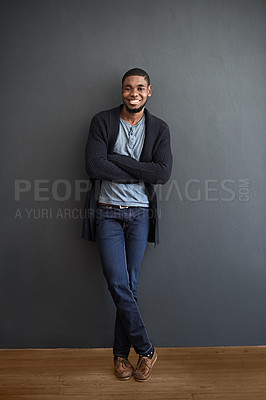 Buy stock photo Portrait of a smiling young man standing with his arms crossed against a gray wall