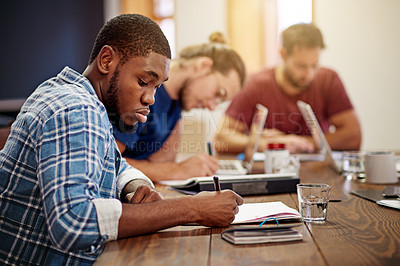 Buy stock photo Shot of a young man writing in notebook while sitting at a table in an office with colleagues in the background