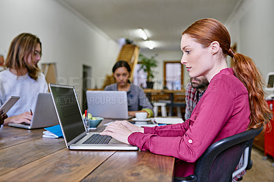 Buy stock photo Shot of a young woman using a laptop at a table in an office with colleagues in the background