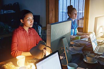 Buy stock photo Shot of a young woman working on a computer in an office in the evening