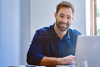 Buy stock photo Portrait of a smiling man sitting at a desk in an office working on a laptop