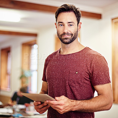 Buy stock photo Portrait of a man standing in an office using a digital tablet with colleagues in the background