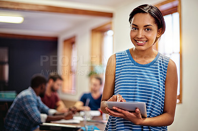 Buy stock photo Portrait of a smiling young woman standing in an office using a digital tablet with colleagues in the background