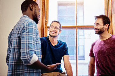 Buy stock photo Shot of three male colleagues talking together while standing in an office