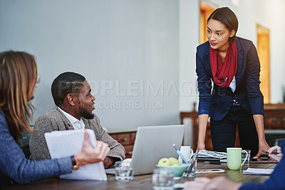 Buy stock photo Shot of a manager leaning on a table in an office during a meeting