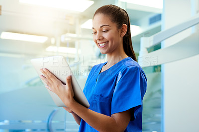 Buy stock photo Shot of a young nurse using a tablet while standing inside a clinic