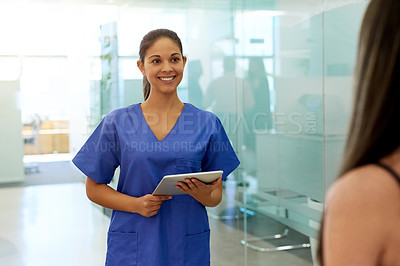 Buy stock photo Shot of a friendly young nurse greeting a patient in the clinic