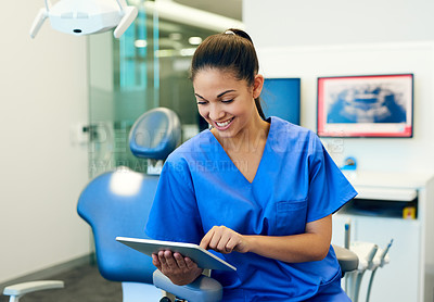 Buy stock photo Cropped shot of a young female dentist using a digital tablet in her dental office