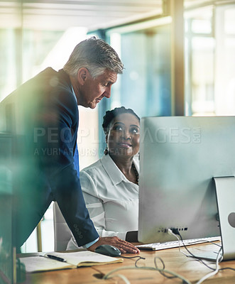 Buy stock photo Shot of two businesspeople working together at a computer in the office