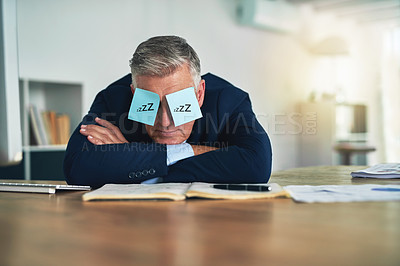 Buy stock photo Shot of a tired businessman napping at his desk with adhesive notes on his eyes