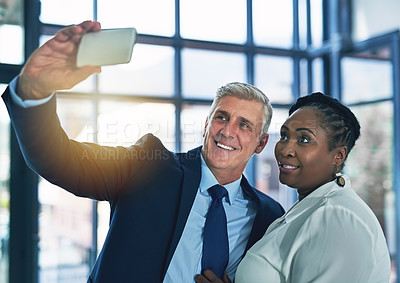Buy stock photo Shot of two happy businesspeople posing for a selfie together in the office