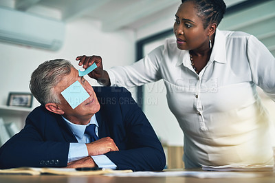 Buy stock photo Shot of a businesswoman removing adhesive notes from her coworker's eyes as he sleeps at his desk