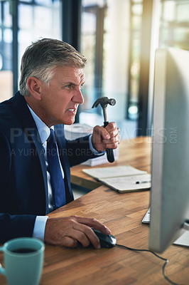 Buy stock photo Shot of a frustrated businessman threatening to hit his computer screen with a hammer