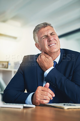 Buy stock photo Shot of a wincing businessman holding his stiff neck while sitting at a desk in the office
