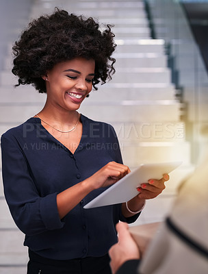Buy stock photo Shot of a happy businesswoman using a tablet while accepting a package from a courier in the office