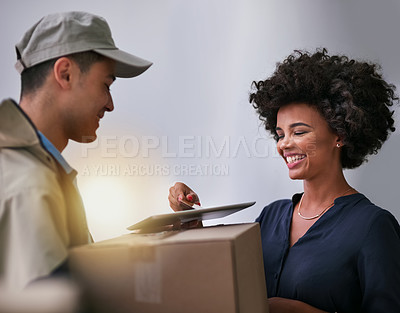 Buy stock photo Shot of a happy businesswoman using a tablet to sign for a package delivered to her office