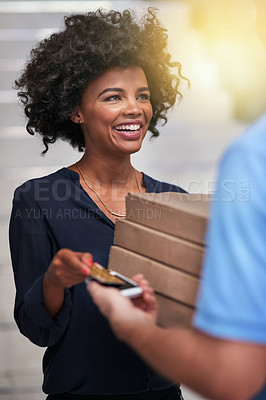 Buy stock photo Shot of a happy businesswoman accepting a pizza delivery from an unidentifiable delivery man in the office