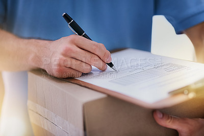 Buy stock photo Shot of an unidentifiable delivery man filling in paperwork while out on a delivery