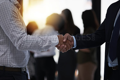 Buy stock photo Shot of two silhouetted businesspeople shaking hands in front of a window in the office