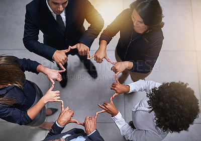 Buy stock photo High angle shot of a group of coworkers making a shape with their hands in the office