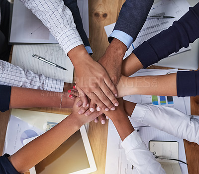 Buy stock photo High angle shot of a group of businesspeople putting their hands in a pile in the office