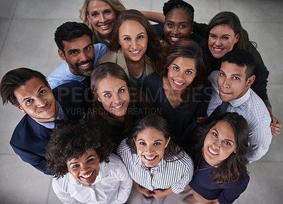 Buy stock photo High angle shot of a group of coworkers looking up while standing together in the office