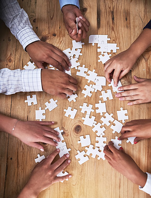 Buy stock photo High angle shot of a group of unidentifiable businesspeople building a puzzle together in the office