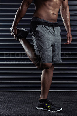 Buy stock photo Cropped shot of an unrecognizable man stretching before a workout