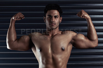 Buy stock photo Cropped portrait of an athletic young man flexing his biceps against a dark background
