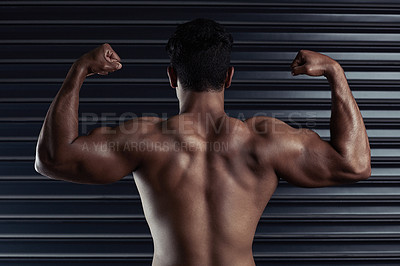 Buy stock photo Rearview shot of an athletic young man flexing his biceps against a dark background
