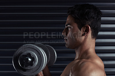 Buy stock photo Cropped shot of an athletic young man working out with a dumbbell
