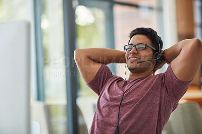 Buy stock photo Shot of a call centre agent looking relaxed at his desk