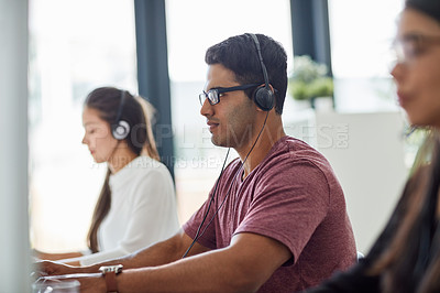 Buy stock photo Shot of a group of customer service representatives working at a desk