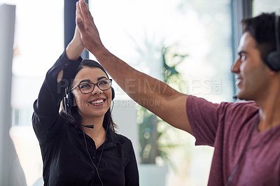 Buy stock photo Shot of two call centre agents giving each other a high five at the office