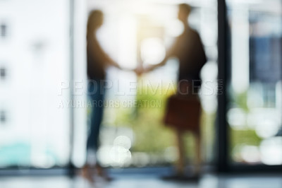 Buy stock photo Defocussed shot of two silhouetted businesspeople shaking hands in front of a window in the office