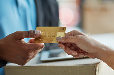 Buy stock photo Cropped shot of a customer using a credit card to pay for a delivery made by a courier