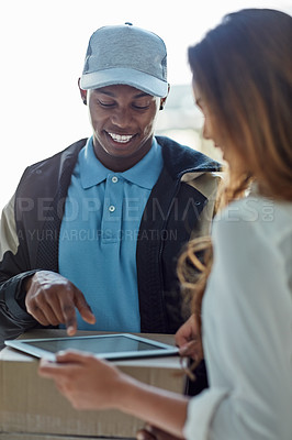 Buy stock photo Cropped shot of a businesswoman using a tablet to sign for a package delivered to her office