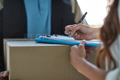 Buy stock photo Cropped shot of a woman signing for a package delivered by a courier