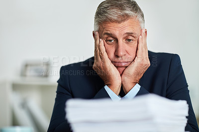 Buy stock photo Shot of a mature businessman looking at paperwork and feeling overwhelmed