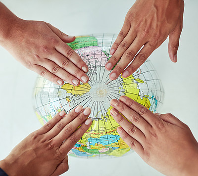 Buy stock photo High angle shot of a group of unrecognisable people with their hands on a world globe